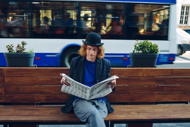 Рыжий битник человек сидит на скамейке с газетой