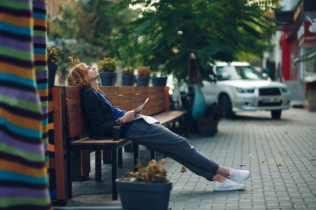 長い木製のベンチに横たわっている間夢を見る男