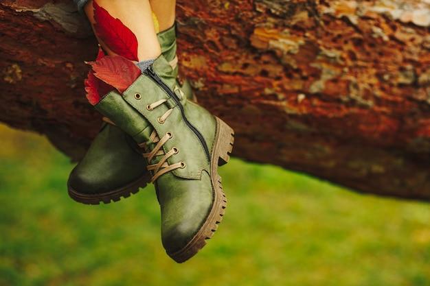 女性の足に緑の革のブーツ