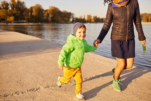 Мама и сын веселятся на берегу озера