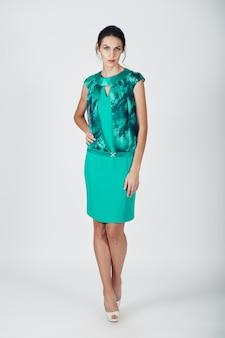 ターコイズブルーのドレスの若い壮大な女性のファッション写真