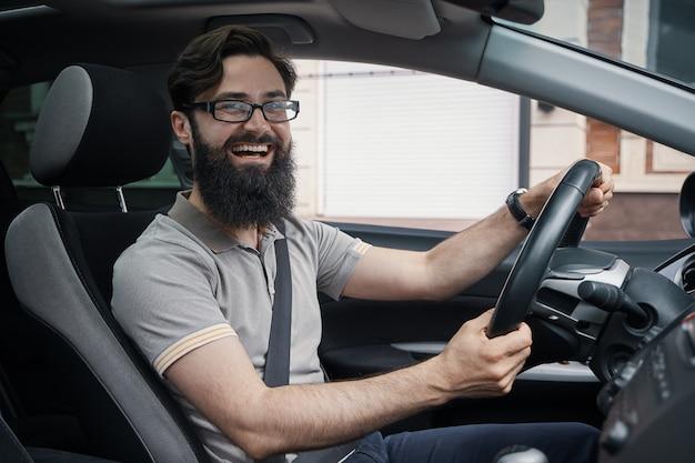 Счастливый харизматичный мужчина за рулем автомобиля