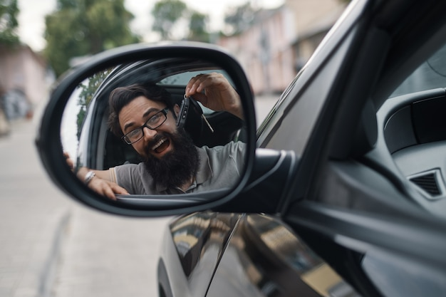 車のキーを保持しているカリスマ的な男