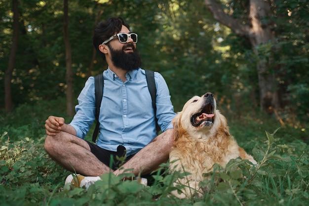 座っている彼の犬と一緒に足を組んで草で休んで男