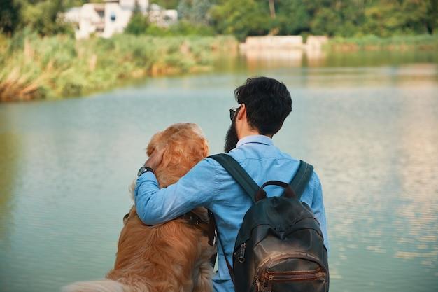 Молодой человек сидит со своей собакой на стуле в парке