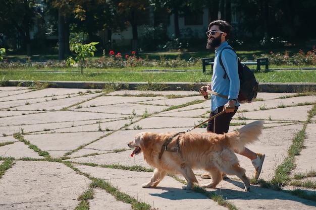 公園で彼の犬を歩く男