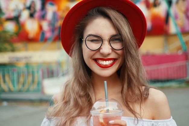 Веселая молодая женщина, держащая напиток во время улыбки