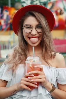 ほほ笑みながら飲み物を保持している陽気な若い女性