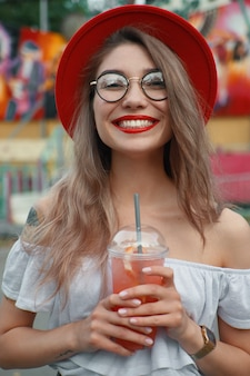 Веселая молодая женщина, держащая напиток, улыбаясь, показывая зубы