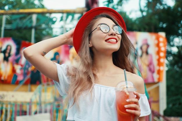 Красивая молодая женщина, держа напиток во время улыбки