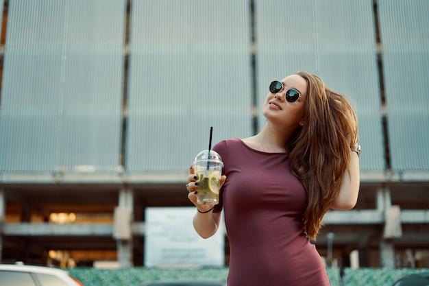 Жизнерадостная женщина на улице пить утренний освежающий напиток