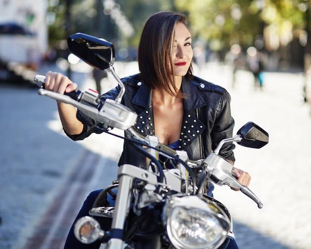 オートバイの革のジャケットのバイク少女