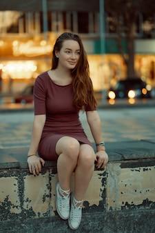 Красивая одинокая девушка, сидя в городе с света в спину