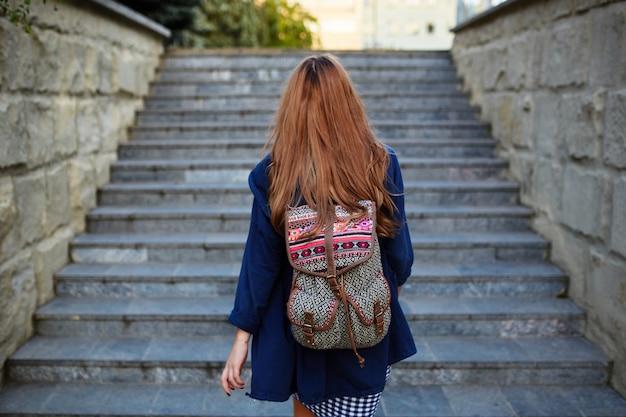 階段を登るバックパックを持つ学生少女