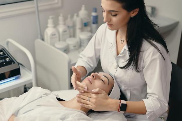 Молодая женщина лежит с закрытыми глазами, косметолог делает процедуру