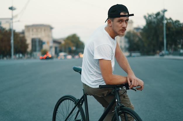 自転車に座ってポーズをとって若いハンサムな男