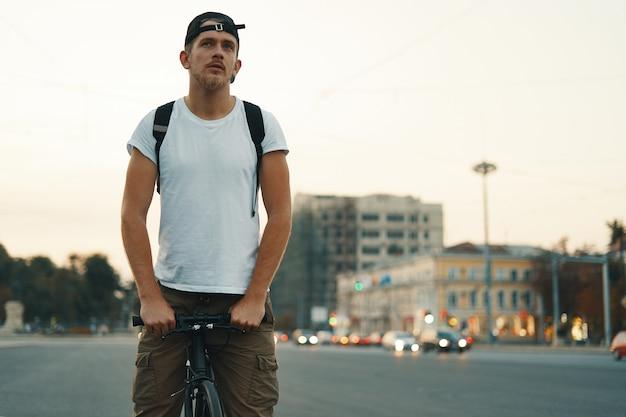 ぼやけた街、ハンドルバーに手を繋いでいる都市で男乗馬自転車