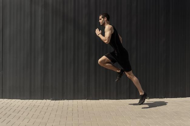 Снимок сбоку подходят молодой, спортивный человек прыгает и работает.