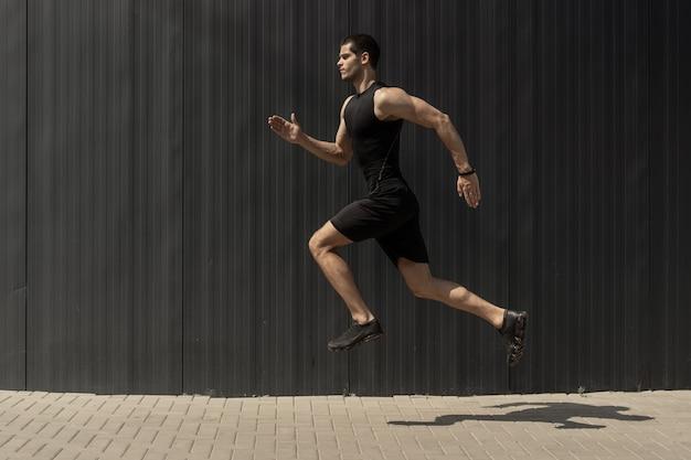 ジャンプして実行しているフィットの若い、運動男の側面図ショット。