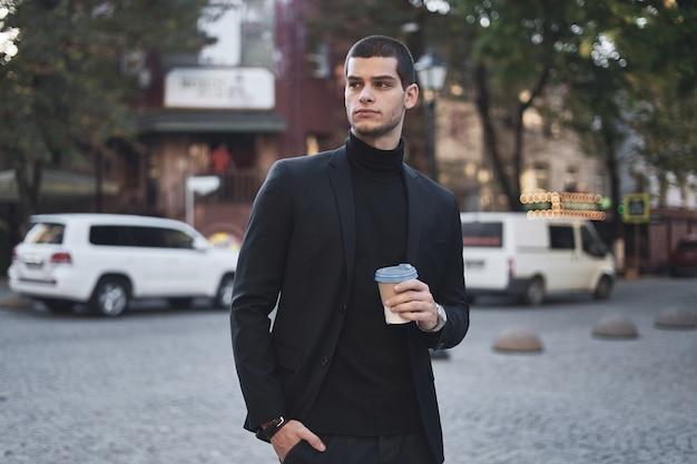 Молодой предприниматель собирается на работу с кофе