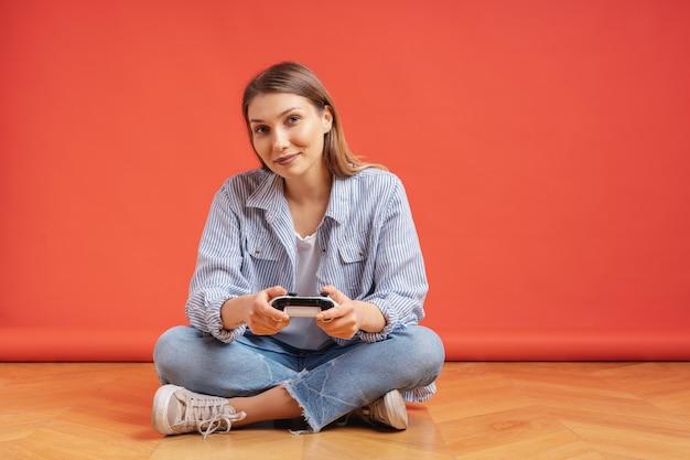 Возбужденный случайный молодая женщина, играя в видеоигры, развлекаясь на красном