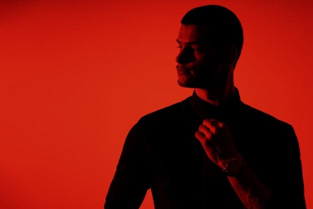Силуэт молодого уверенно красивого бизнесмена нося черную рубашку в красном свете