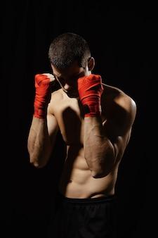 包帯で手で自信を持って防御的な姿勢でポーズをとってボクサー男性戦闘機