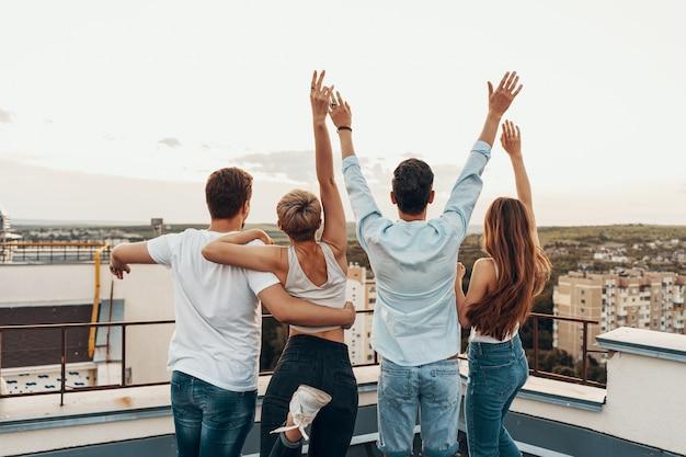Группа друзей, наслаждаясь на открытом воздухе на крыше