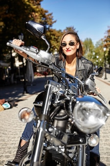 Байкер девушка в кожаной куртке на мотоцикле