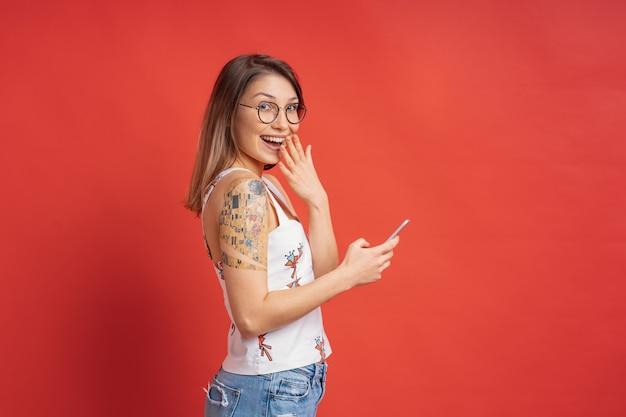 Удивленная милая девушка с телефоном в руках на красной стене