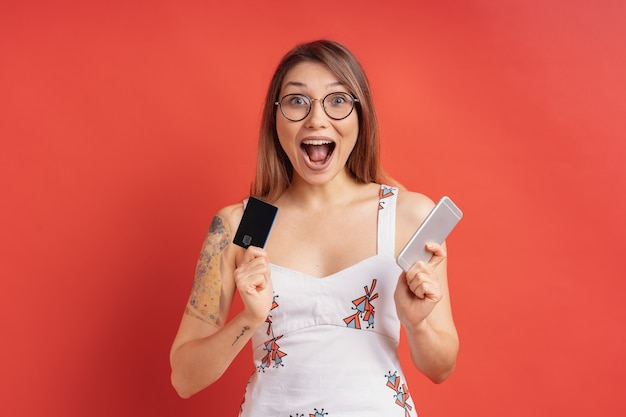 彼女の手で携帯電話とクレジットカードを保持しているかなり若い女性を興奮