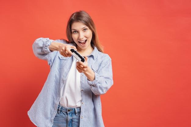 Возбужденная случайная молодая женщина, играющая в видеоигры с удовольствием на красной стене
