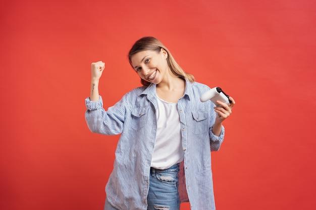 競争力のある女の子は、赤い壁にゲームジョイスティックコントローラーを保持している勝利を祝います。
