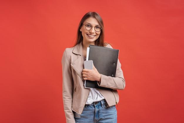 若い笑顔の学生または赤い壁のフォルダーと立っている眼鏡のインターン。
