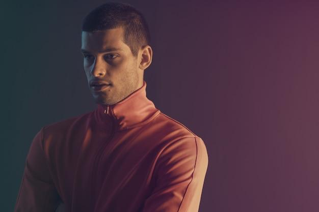 魅力的な男性モデルのクローズアップの肖像画。カラーフラッシュライト