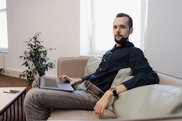 若い男がオフィスのソファーに座ってラップトップに取り組んで