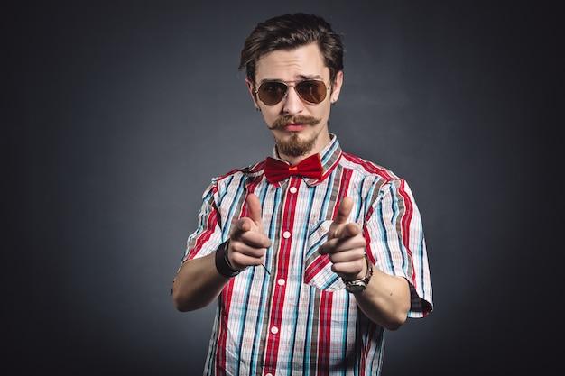 スタジオでメガネを格子縞のシャツと蝶ネクタイの男