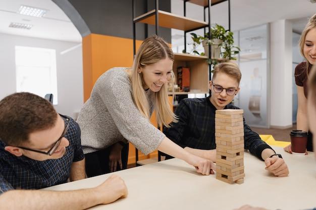 混合チームがオフィスで木製のゲームをブロック