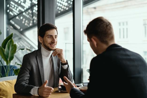Двое молодых бизнесменов обсуждают что-то