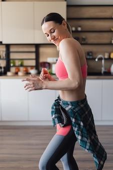 自分と人生を楽しんでいる台所の真ん中で踊る陽気な女性