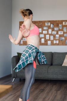 リビングルームの真ん中で踊って、自分と人生を楽しんでいる笑顔の女性
