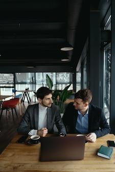 Два молодых бизнесмена, имеющие успешную встречу в ресторане.