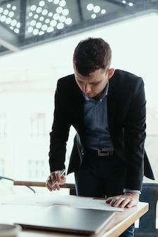 近代的なオフィスでドキュメントに署名する成功するビジネス人