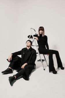 ファッショナブルな男と階段の上に座っている女性