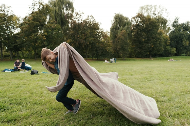 公園で空飛ぶ毛布で走っている陽気な少年