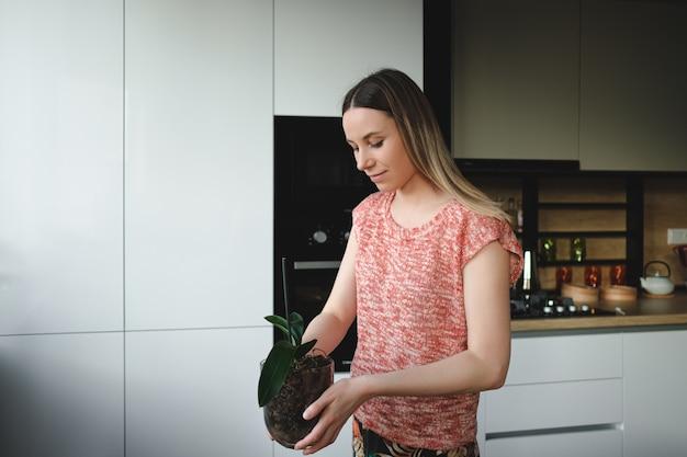 Женщина расставляет цветы в доме