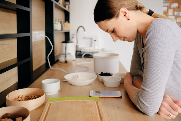 Женщина смотрит на рецепт по телефону