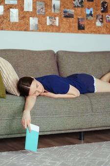 居間のソファーで読書しながら眠る女性