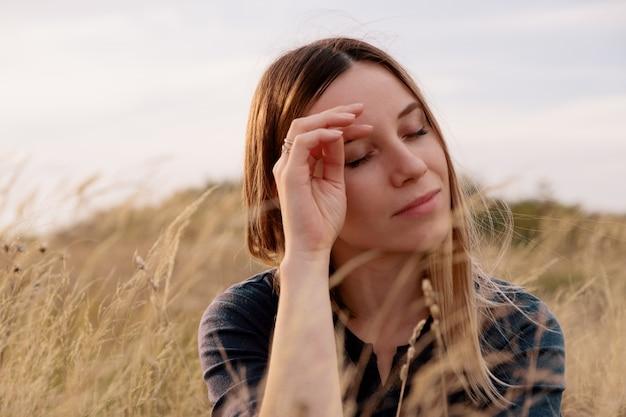 Портрет прекрасной молодой женщины расслабляющий в поле