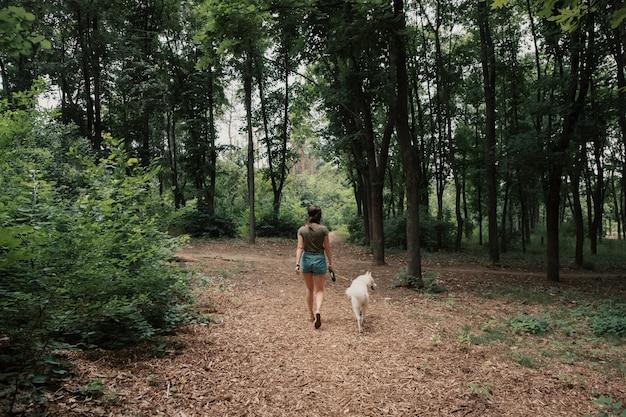 Молодая женщина гуляя с белой лайкой
